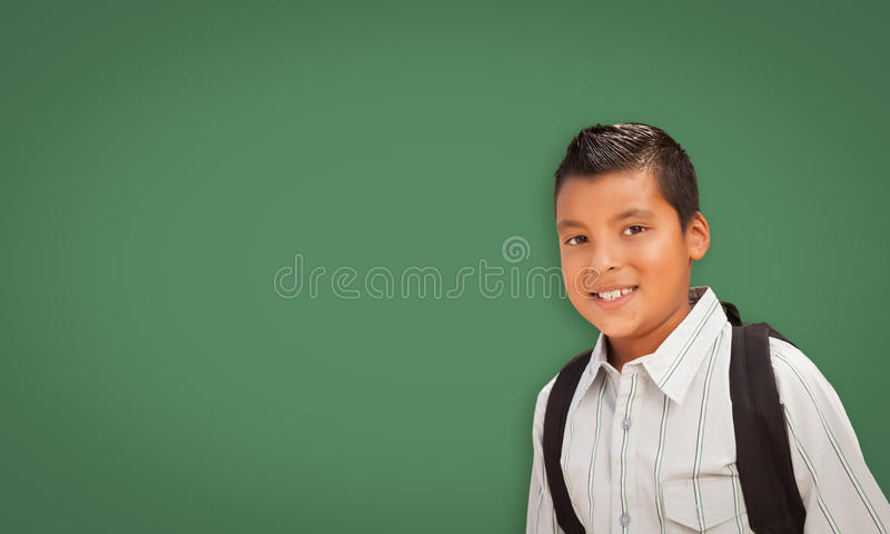 Cute Hispanic Boy In Front of Blank Chalk Board stock photo
