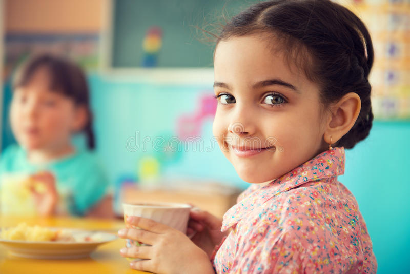Cute hispanic girl drinking milk at school royalty free stock image