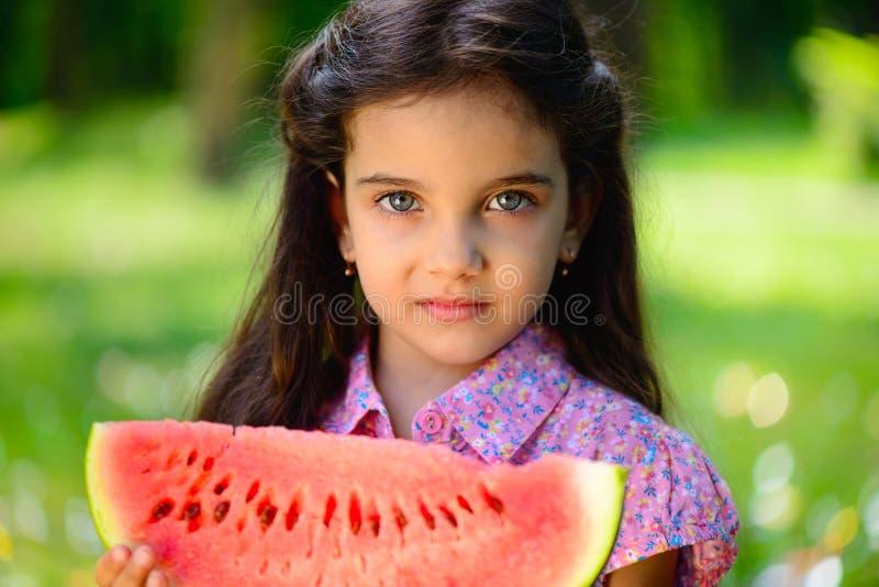 Cute hispanic girl eating watermelon. At park stock photography