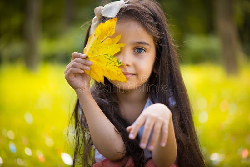 Cute hispanic girl hiding over yellow leaf stock photo