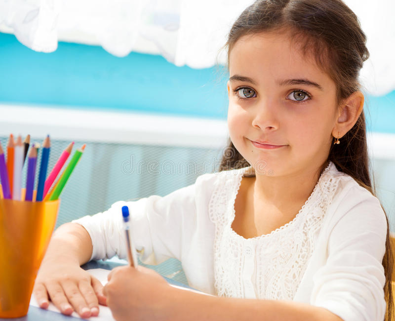 Cute hispanic girl writing at school royalty free stock images