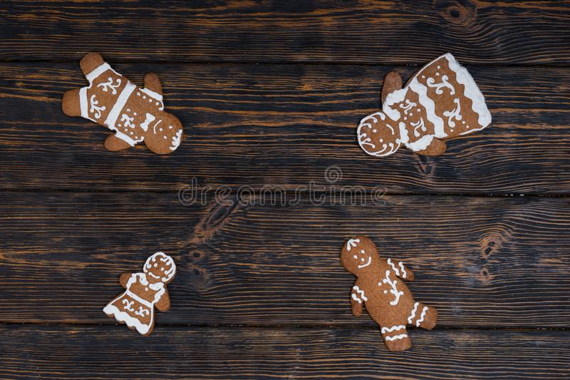 Cute homemade gingerbread family on dark wooden background. Mockup for seasonal offers and holiday post card royalty free stock images