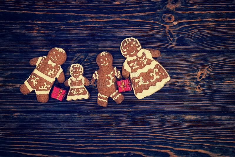 Cute homemade gingerbread family with small red gifts on dark wooden background. Mockup for seasonal offers and holiday post card stock photos