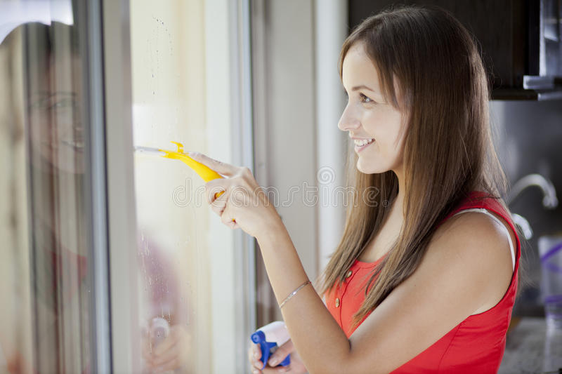 Cute housewife cleaning the windows. Pretty young woman cleaning a glass door inside the house royalty free stock photo