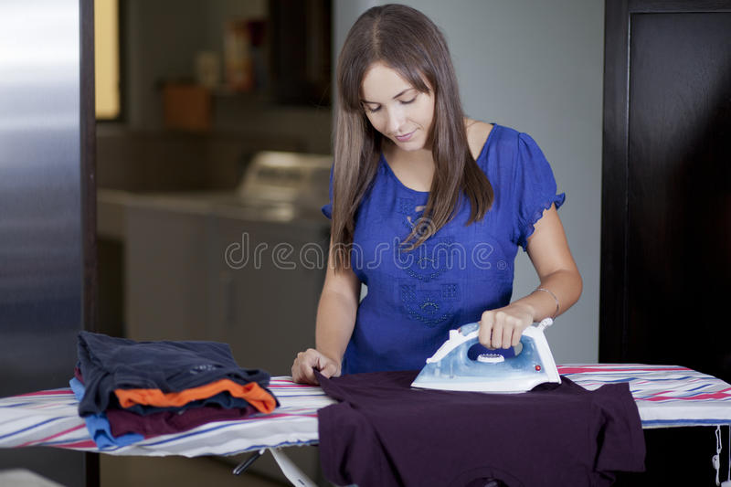 Cute housewife ironing clothes. Young beautiful woman doing some house chores royalty free stock photo