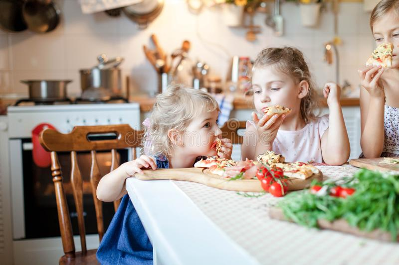 Cute hungry kids are enjoying delicious food in cozy home kitchen. royalty free stock photography