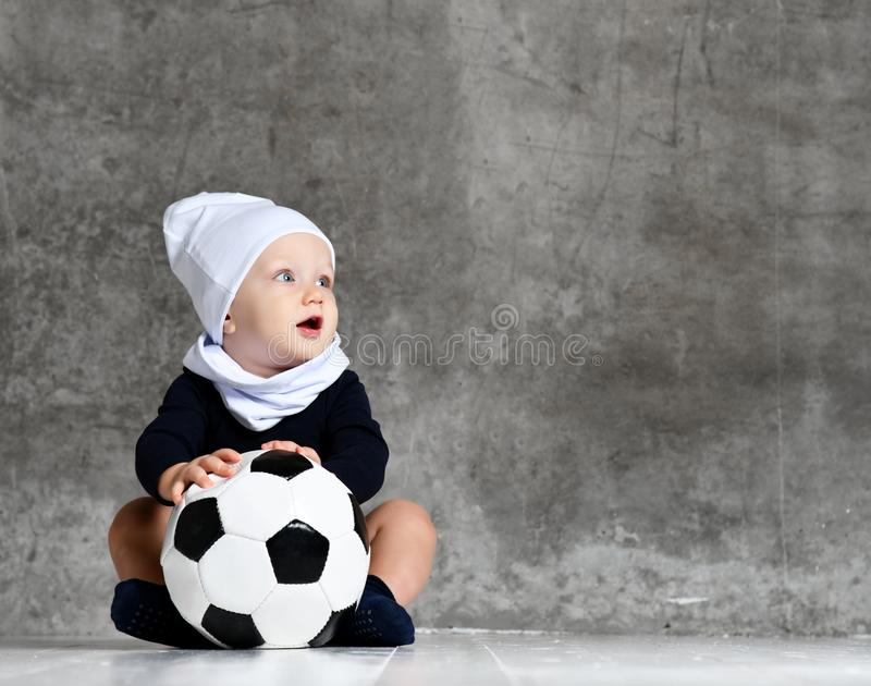 Cute image of baby holding a soccer ball. stock photo