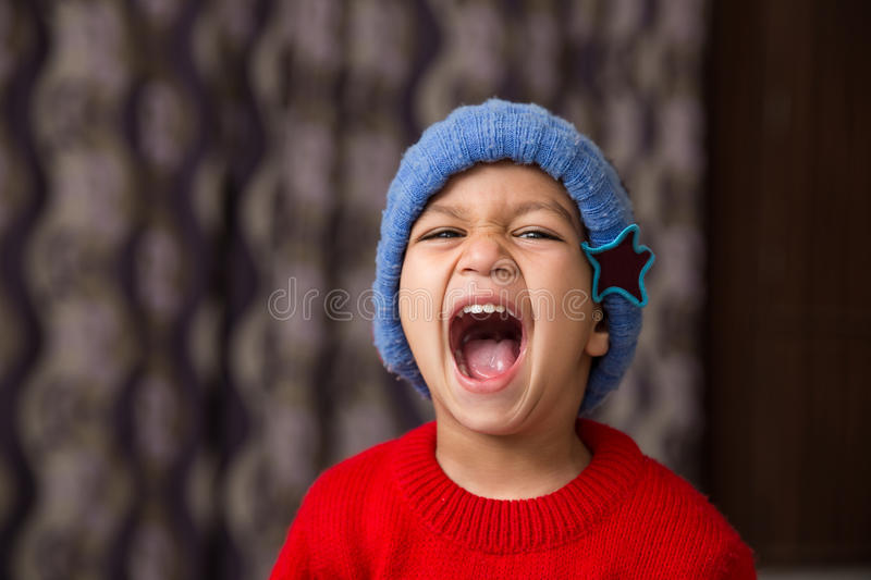 Cute Indian Kid striking a pose in winter wear with a big laugh. Cute Indian Kid striking a pose wearing red sweater and blue cap with a big laugh avaialble with stock photography
