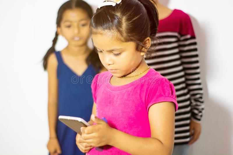 Cute Indian little kid using mobile device and two kids watching the phone from her behind.  stock photography