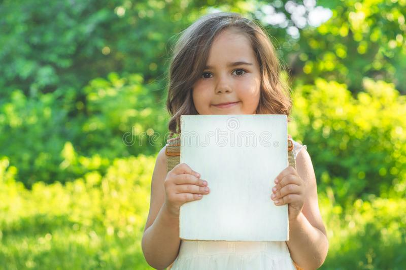 Cute industrious child is standing with a book and a briefcase outdoors. Little Girl reading the book royalty free stock photography