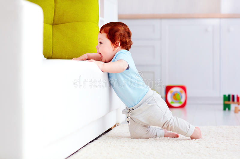 Cute infant baby boy climbing up the couch at home. Cute happy infant baby boy climbing up the couch at home royalty free stock photos