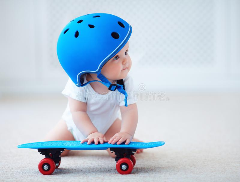 Cute infant baby girl in protective helmet outfit ready to ride skateboard, extreme sport concept stock image