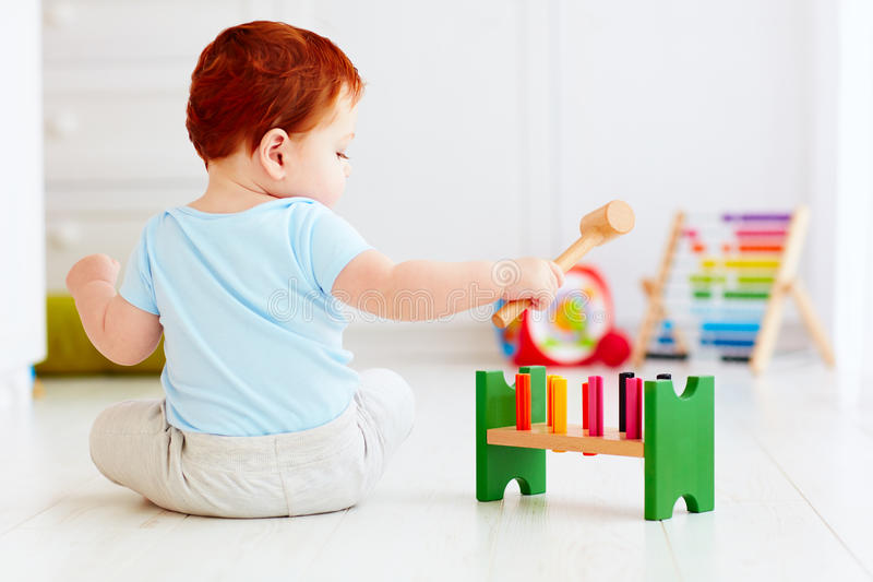 Cute infant baby playing with wooden hammer block toy stock image