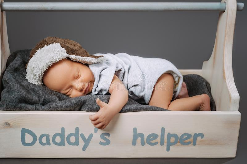 Cute infant baby showing thumb up while sleeping in wooden toolbox with daddys. Helper lettering royalty free stock photo