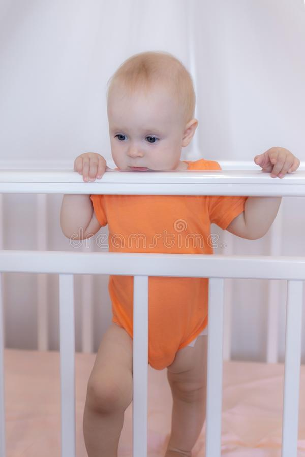 A cute infant baby standing in a crib in a pink bedroom scene stock image