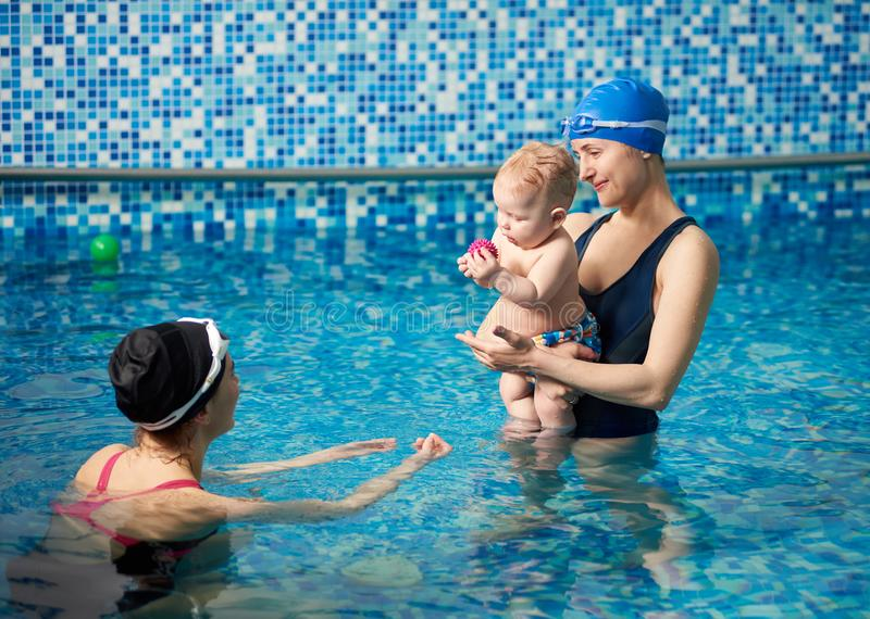 Cute infant having interesting rest time during playing and communication with his swimming instructor in pool water stock images