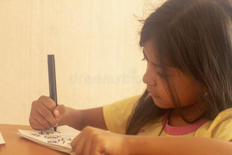 Cute brunette girl doing dubujos on a table. Cute inspired brunette girl, making drawings on her work desk stock photo