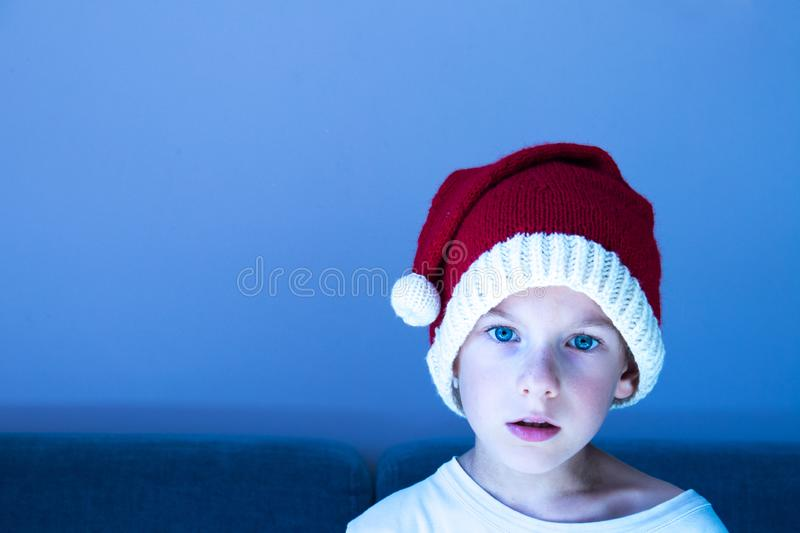 A cute isolated child wearing a knitted Santa hat. Xmas design. With copy space. Enchantment, surprise, astonishment, wonder expression royalty free stock image