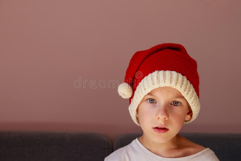 A cute isolated child wearing a knitted Santa hat. Xmas design. With copy space. Enchantment, surprise, astonishment, wonder expression royalty free stock photos