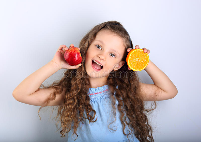 Cute joying grimacing happy kid girl with curly hair style holding citrus orange fruit and red apple in the hands in blue. Background stock images