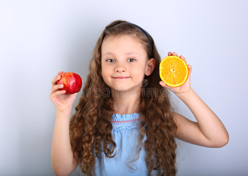 Cute joying smiling kid girl with curly hair style holding citrus orange fruit and red apple in the hands on blue background stock images