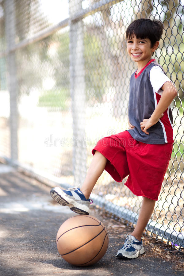 Cute junior boy with basketball stock photography