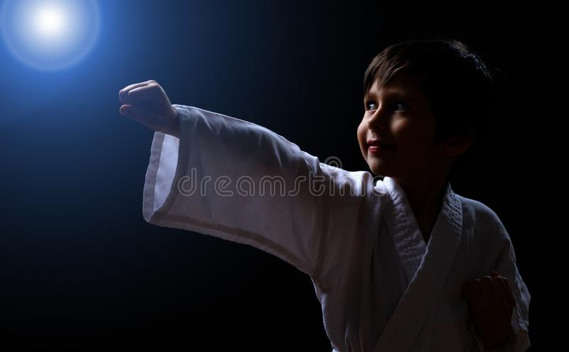 Cute karate boy in white kimono isolated on dark background. Child ready for martial arts fight. Kid fighting at judo training. Best concept for martial fights stock photography