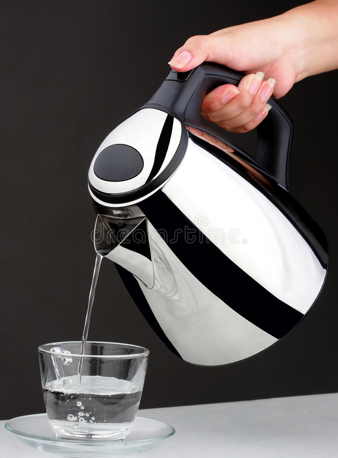 Hand pouring chrome kettle water boiler isolated royalty free stock photography