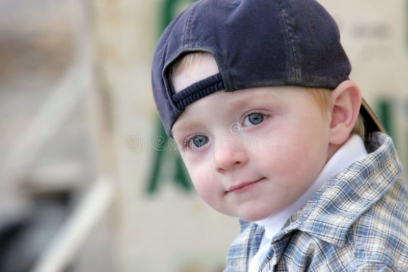 Cute kid with baseball cap. Cute kid wearing his baseball cap backwards royalty free stock photo