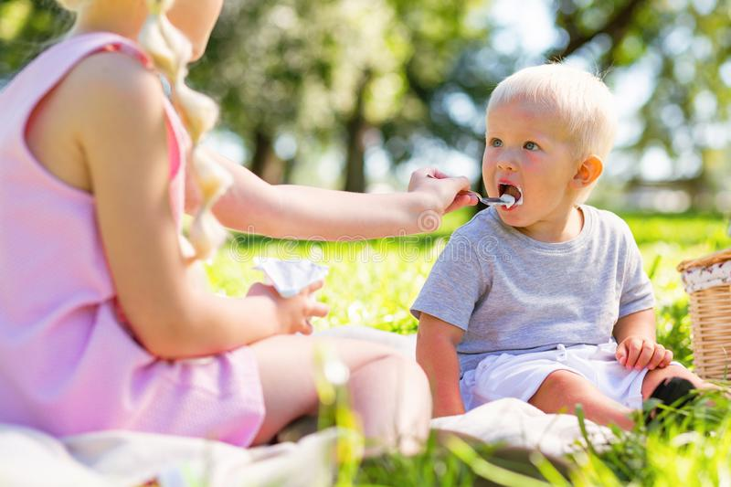 Cute kid being fed by his older sister stock images