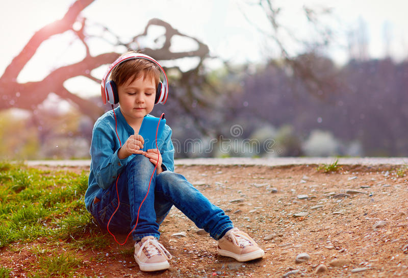 Cute kid boy with headphones listens to the music in park. Cute kid, boy with headphones listens to the music in park stock photo
