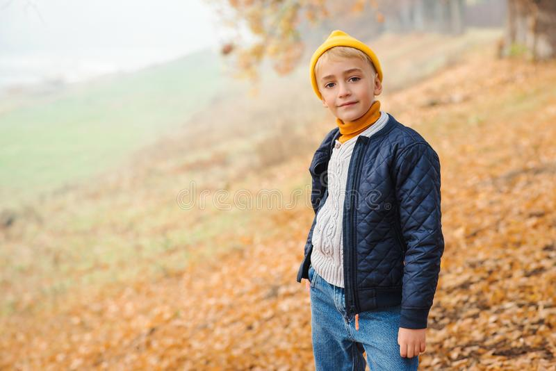 Cute kid boy on a walk in autumn. Kids fashion concept. Autumn mood. Happy boy in autumn park. Boy wearing header and jacket. royalty free stock images