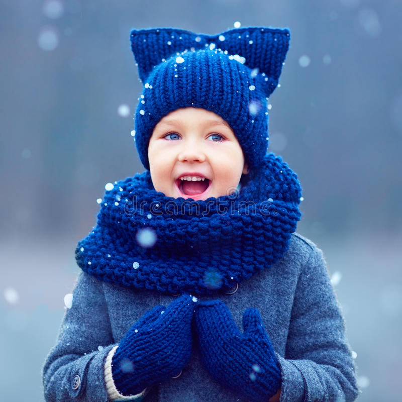 Cute kid, boy in winter clothes playing under the snow royalty free stock photo