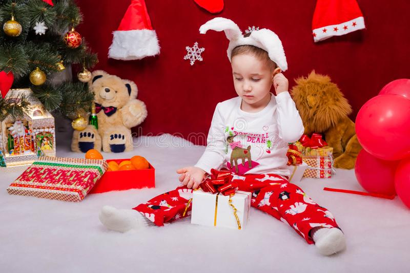 Cute kid in a bunny suit opens a Christmas gift. Interesting kid in a bunny suit opens a Christmas gift from Santa Claus royalty free stock photo