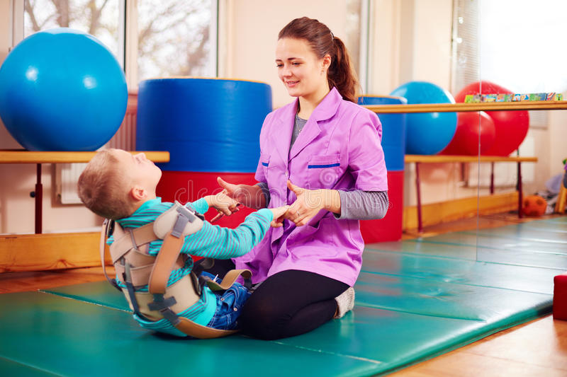 Cute kid with disability has musculoskeletal therapy by doing exercises in body fixing belts. Cute kid boy with disability has musculoskeletal therapy by doing stock photo