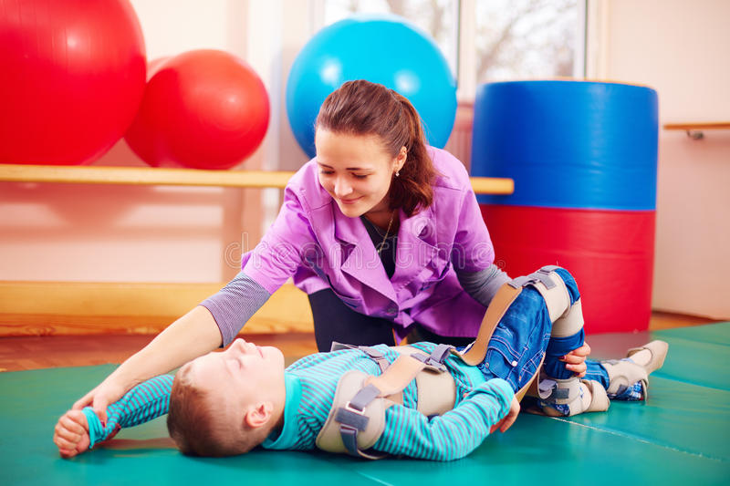 Cute kid with disability has musculoskeletal therapy by doing exercises in body fixing belts. Cute kid boy with disability has musculoskeletal therapy by doing stock photos