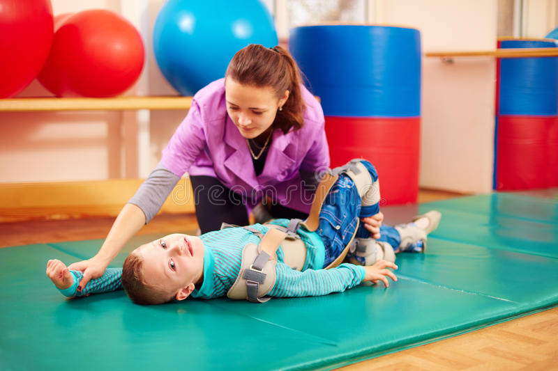 Cute kid with disability has musculoskeletal therapy by doing exercises in body fixing belts. Cute kid boy with disability has musculoskeletal therapy by doing stock image