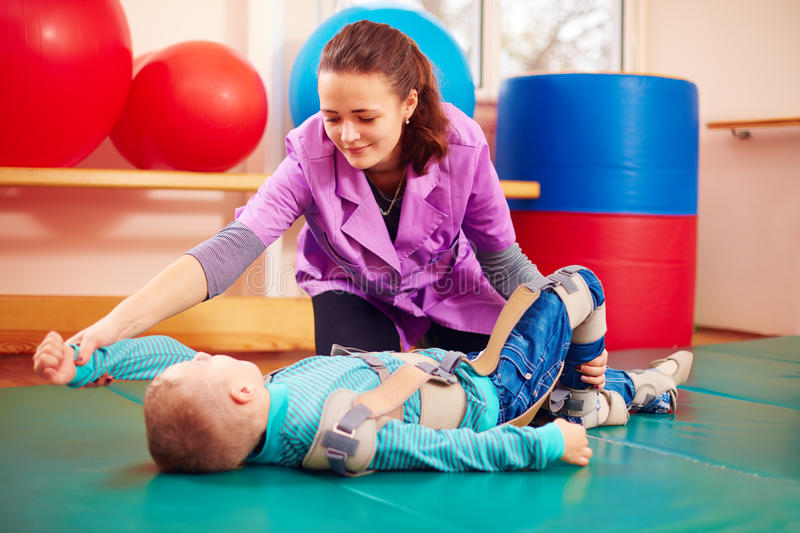 Cute kid with disability has musculoskeletal therapy by doing exercises in body fixing belts. Cute kid boy with disability has musculoskeletal therapy by doing stock photography