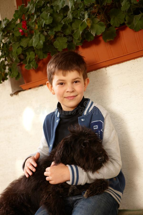 Cute kid with dog. Cute little boy sitting outdoors, hugging black dog royalty free stock photos