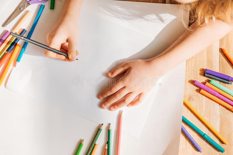 Cute kid drawing on paper with pencils while lying on floor stock image