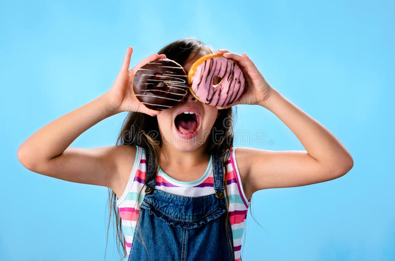 Cute kid eating donut. Portrait of adorable cute girl kid with donut royalty free stock photo