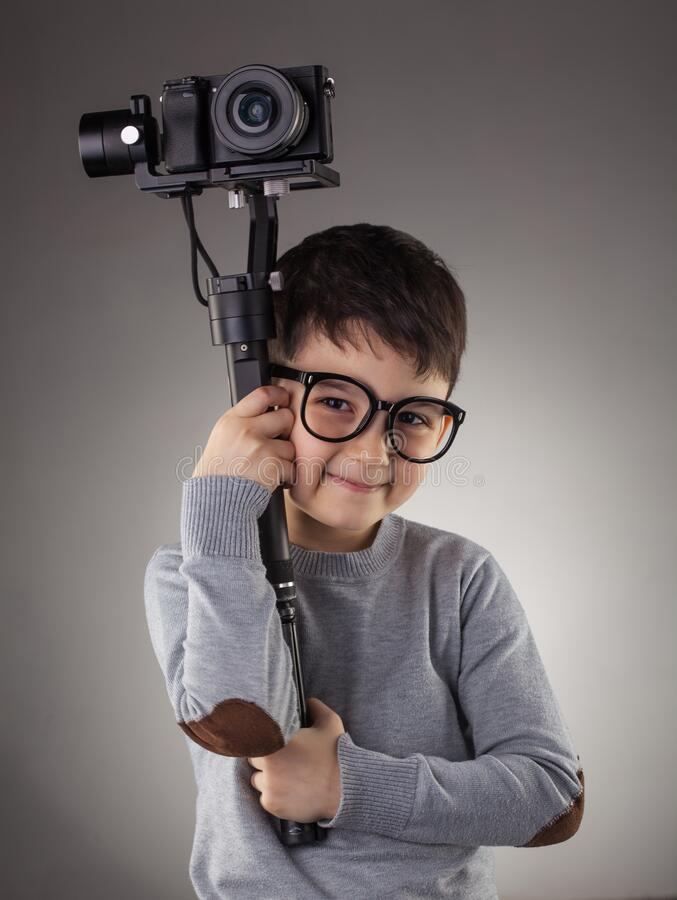 Cute boy with electronic steadicam on the gray background stock photography
