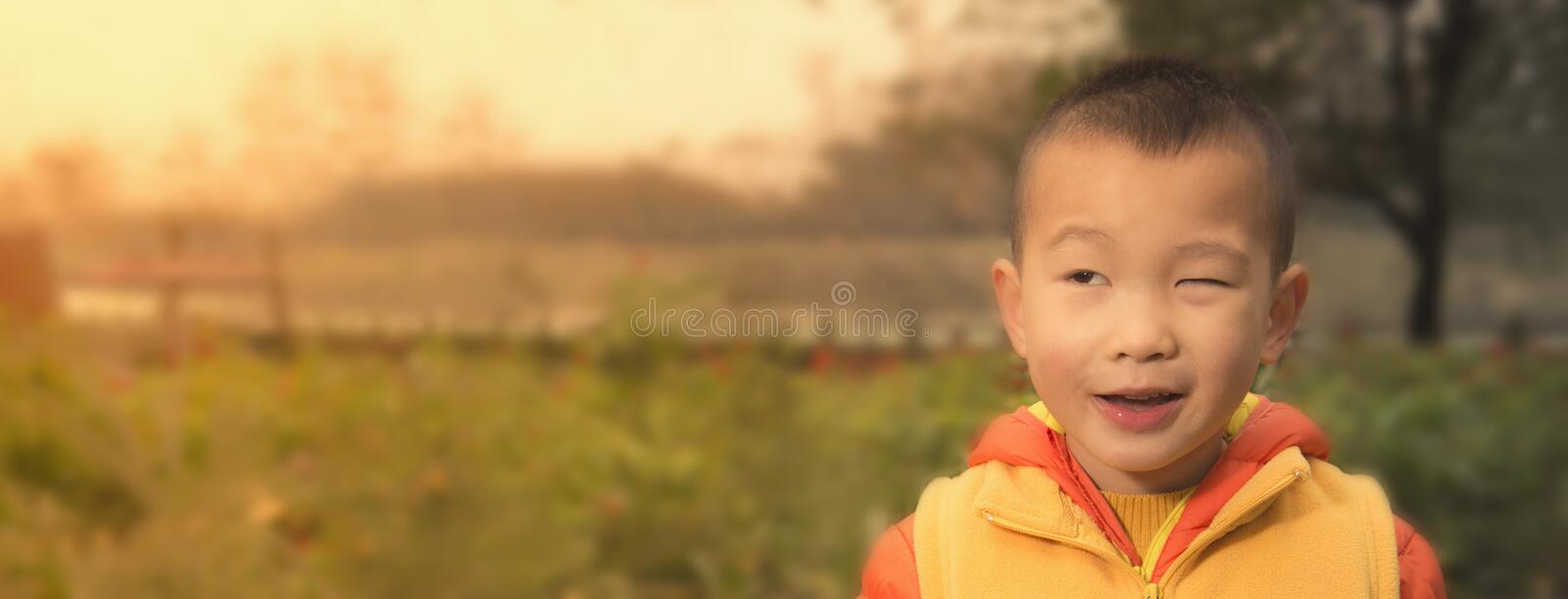 Cute kid expression. Closeup outdoor , closing one eye royalty free stock photography