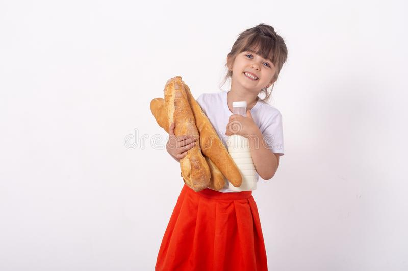Cute kid with French bread in the hands. Freshly baked bread and milk,  on white background. Food for young family with ki royalty free stock photos