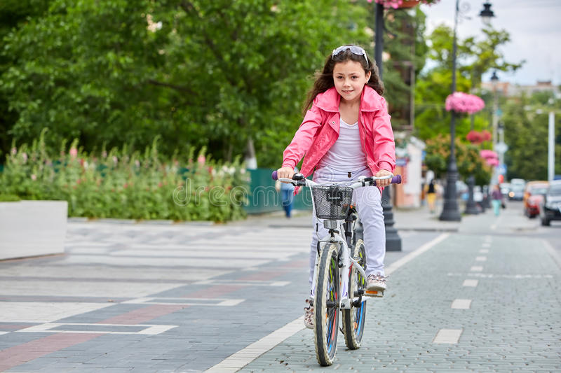 Cute kid girl in blue helmet going to ride her bike stock images