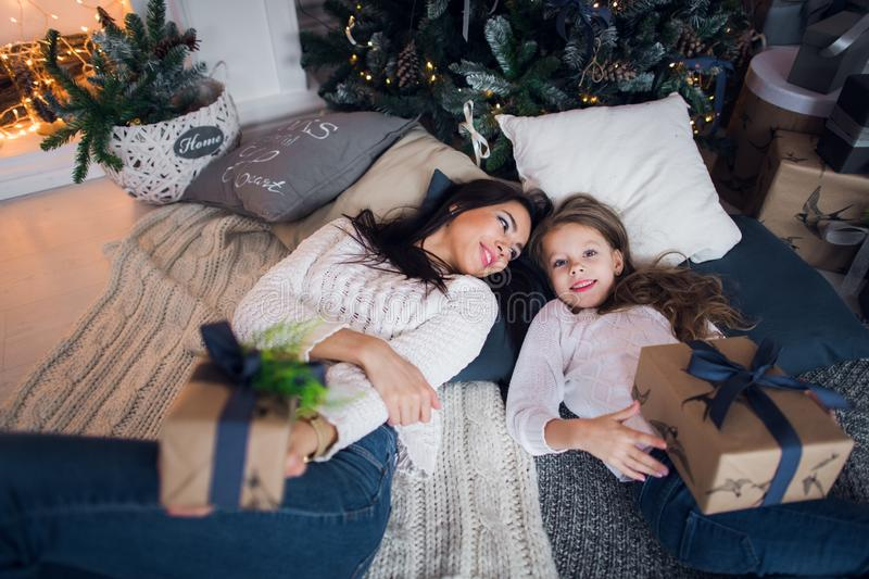 Cute kid girl and her mom playing under christmas tree with presents, lying on wooden floor in room. Wearing trendy royalty free stock photo