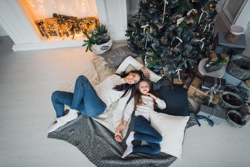 Cute kid girl and her mom playing under christmas tree with presents, lying on wooden floor in room. Wearing trendy stock image