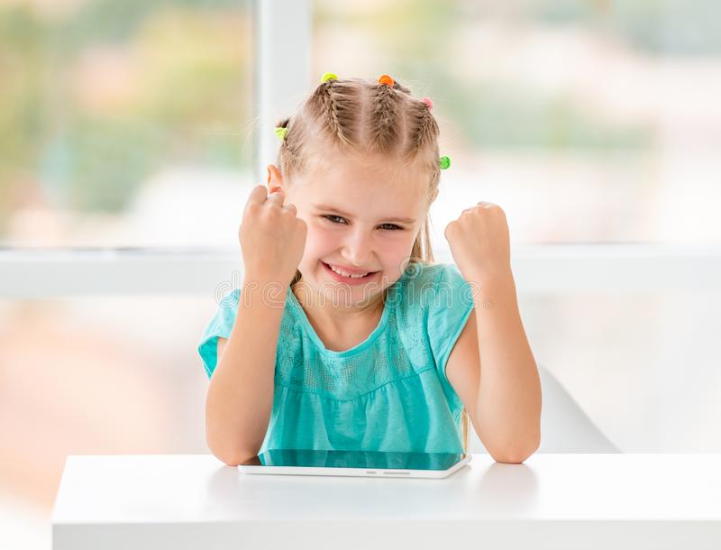 Cute kid girl making fists victory gesture stock photo