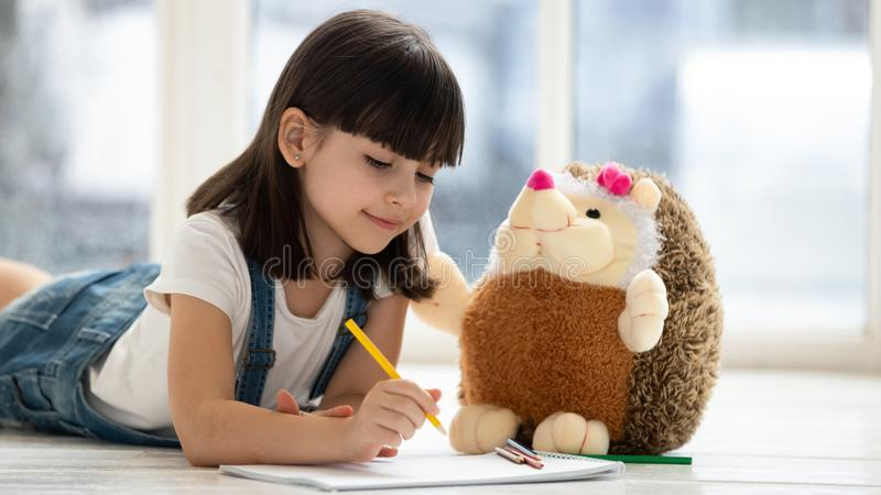 Cute kid girl playing drawing with toy lying on floor stock photos