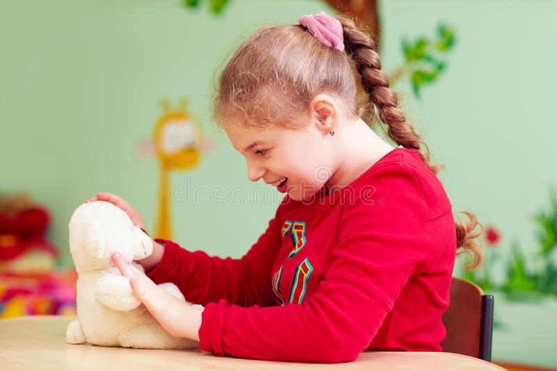 Cute kid girl playing with plush toy in kindergarten for children with special need royalty free stock photography